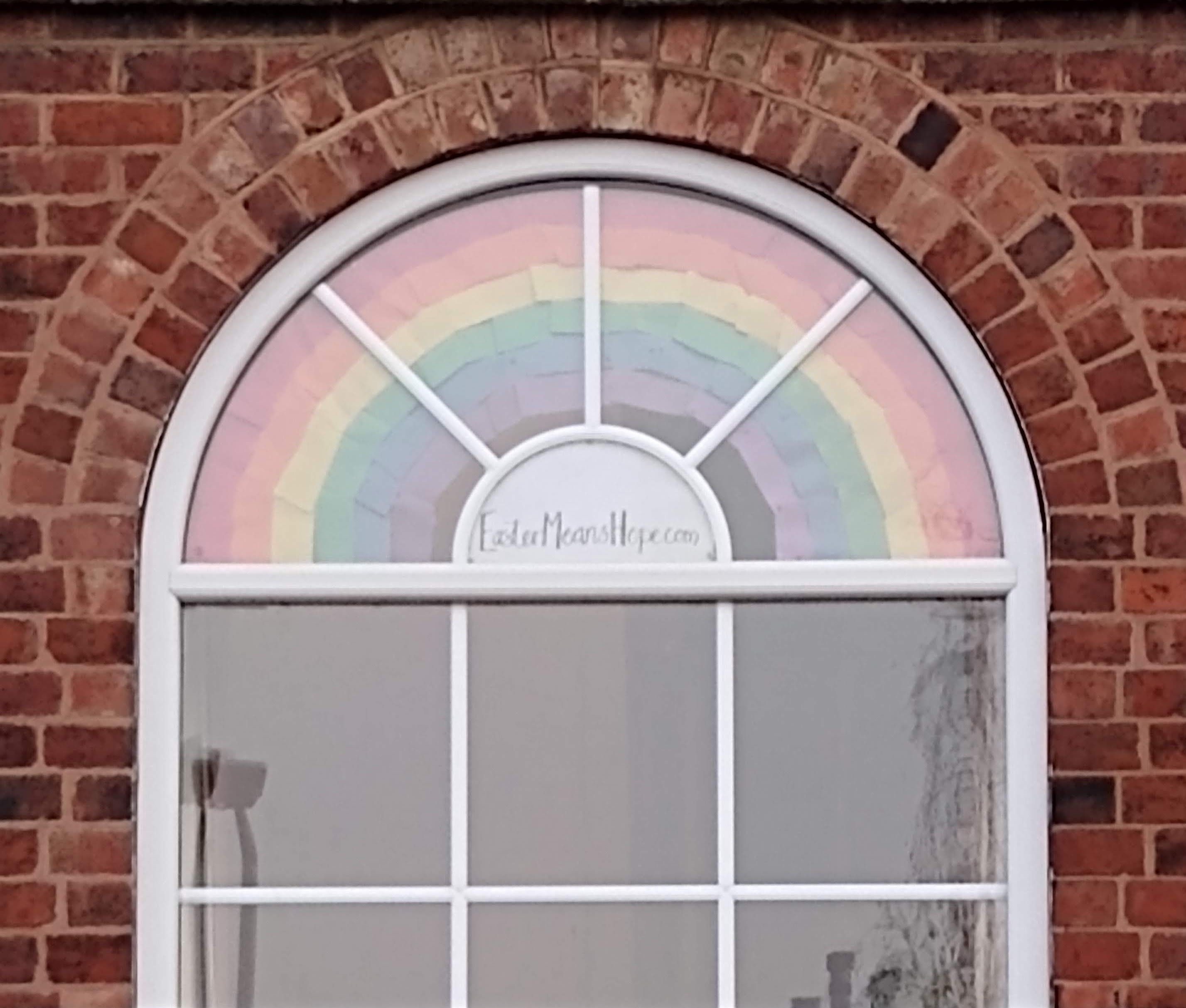 Paper rainbow and 'EasterMeansHope.com' in arched window