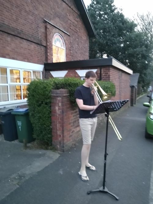 The Joker, wearing black t-shirt and beige shorts, flipflops, plays his trombone outside the Vicarage, using a black music stand.